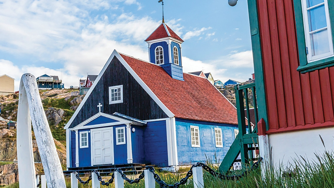 Town of Sisimut, Greenland, on a clear day, with light blue church with red roof, steeple & white trim, beside a red & green building.