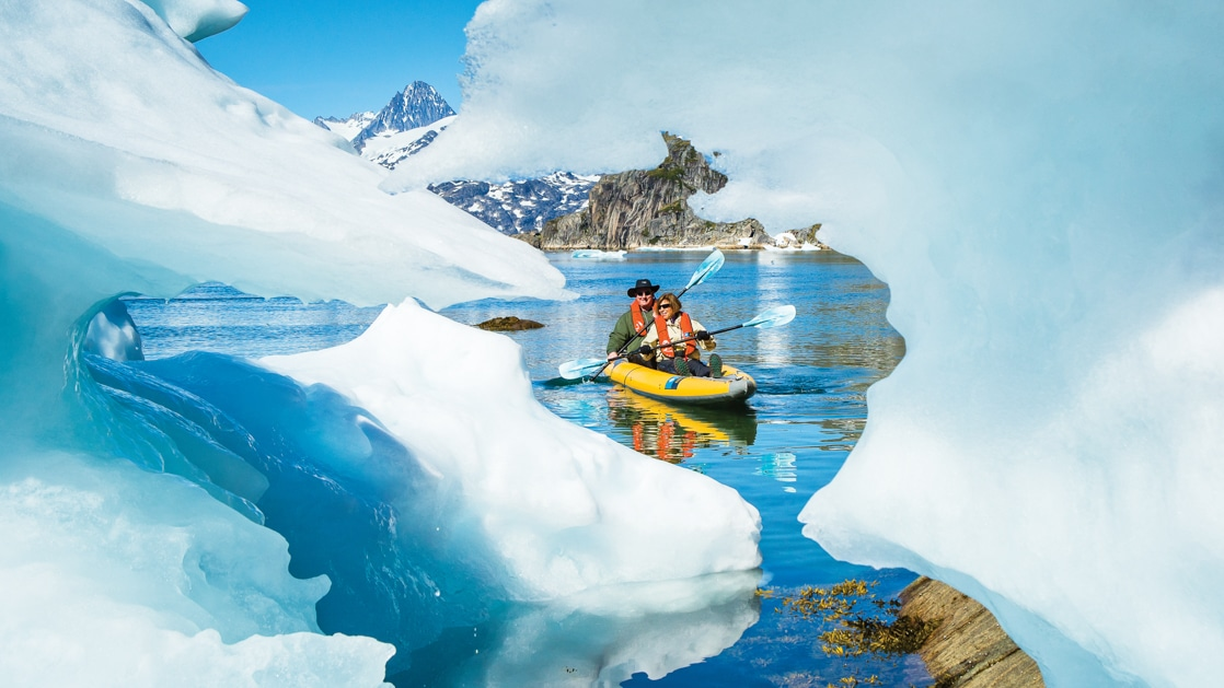 Tandem kayakers paddle around icebergs in glassy water on a sunny day near Skjoldungen Island, Southeastern Greenland.