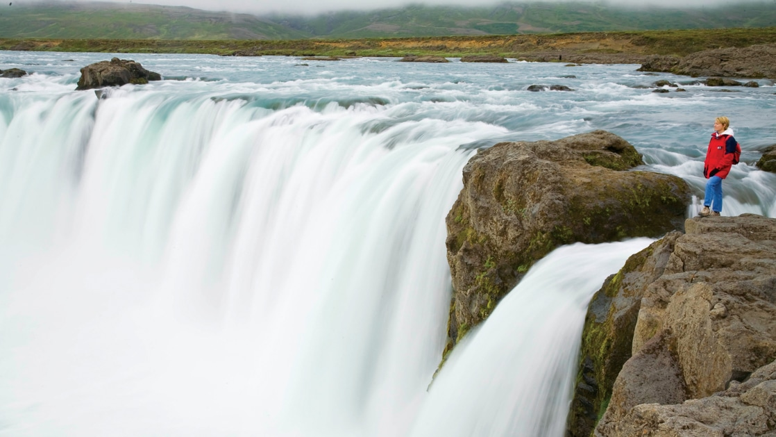 Traveler in a red jacket stands at lip of the giant Godafoss Waterfall of the Gods in Iceland.