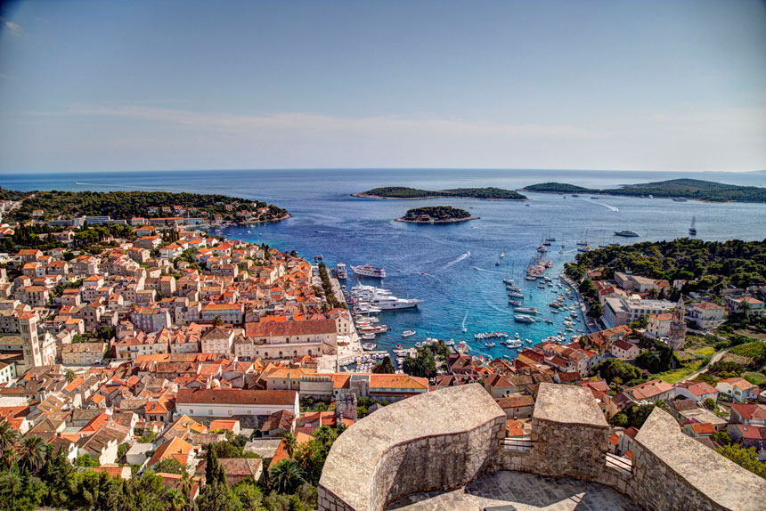 Aerial view of a Croatian port town with terra cotta roofs, beige stone buildings, lush green hillsides, docked small ships & turquoise water.