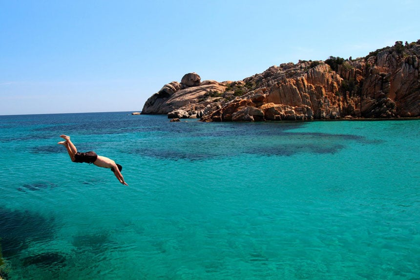 Man dives into turquoise water beside red rocky shoreline on a Mediterranean small ship cruise.