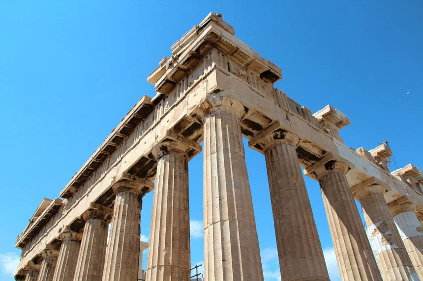 Stone pillars of ancient ruins in Athens, Greece, on a sunny day.