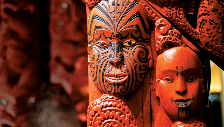 Carved wood pillars with Maori faces in red & black, seen on the National Geographic New Zealand Cruise.