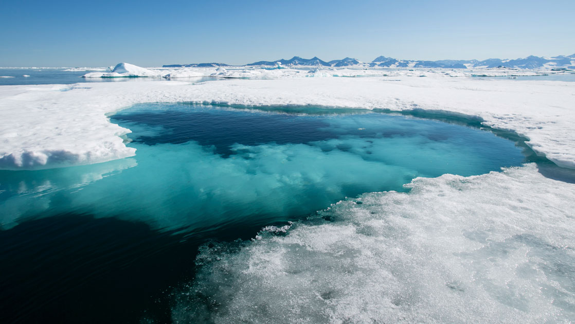 Icy arctic water with turquoise ice below seen on a sunny day during cruises to Iceland and Greenland.