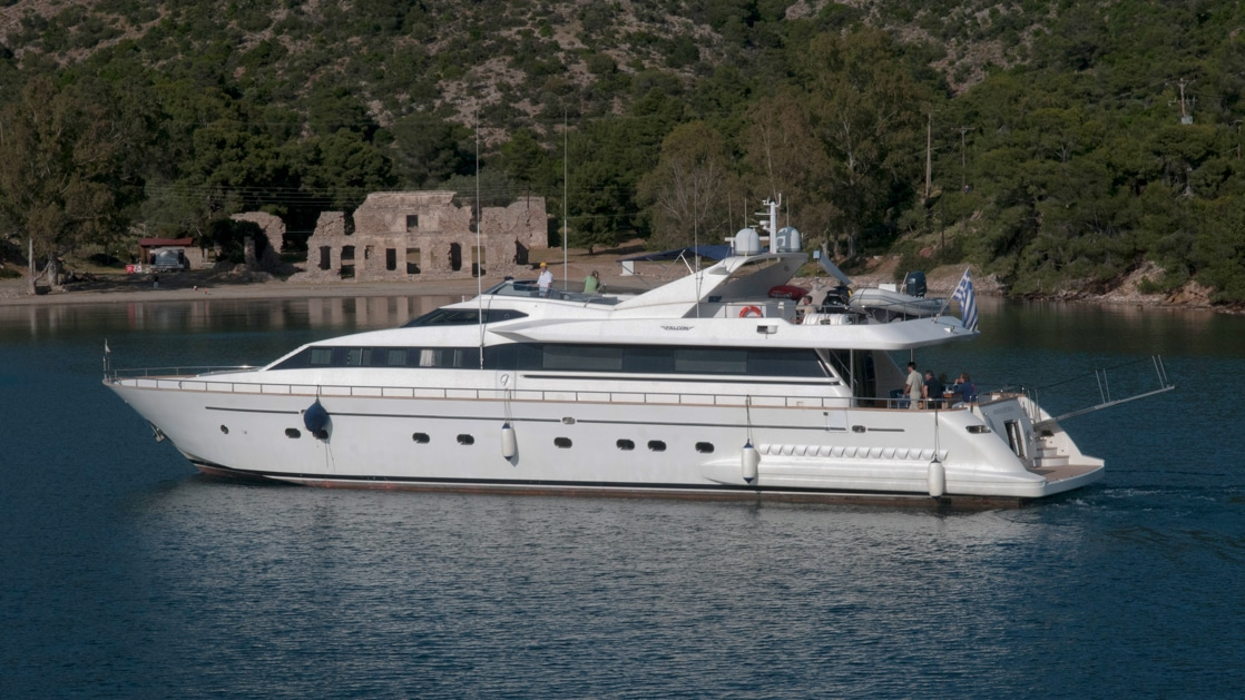 Aerial exterior view of white mega yacht at anchor beside ancient ruins & green hillsides in Greece.
