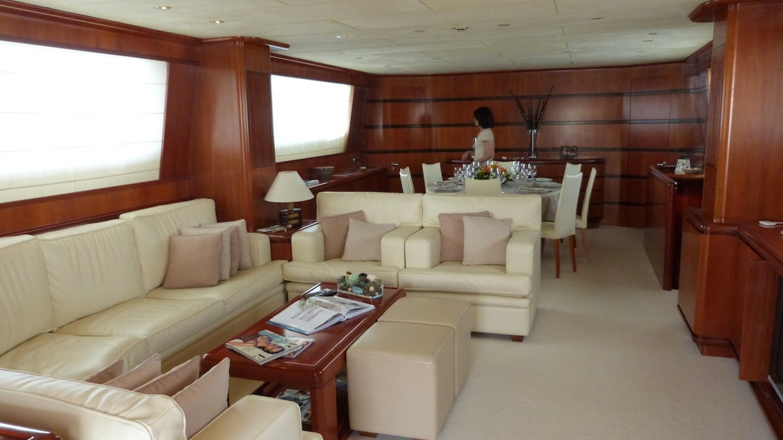 Ship living room beside dining room with wraparound white leather couch, wood coffee table, beige carpet, large windows & wood walls.