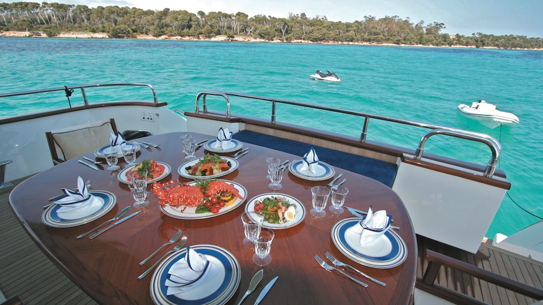 Wood table on outside aft deck of charter yacht, set for a meal, beside turquoise water on a sunny day in Greece.