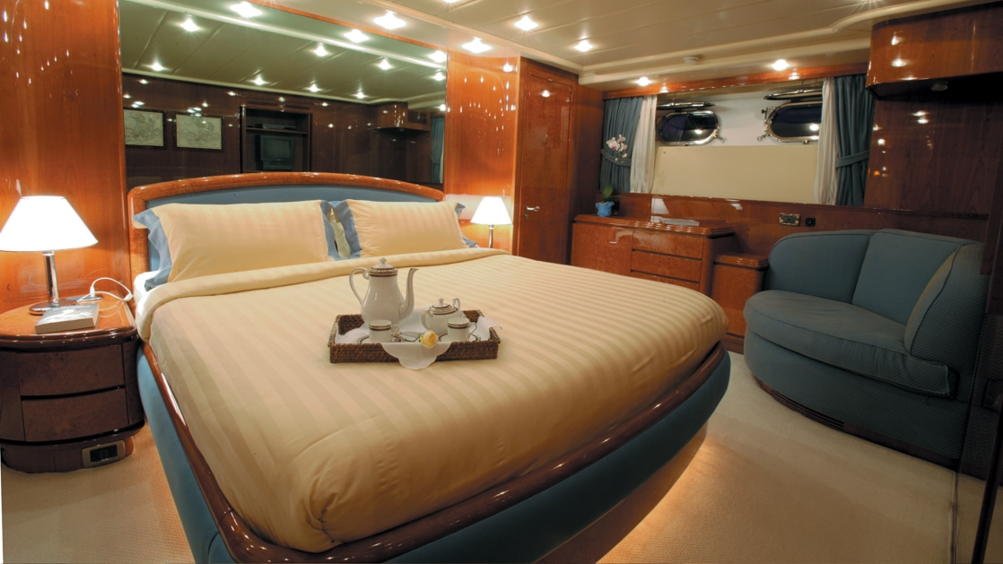 Private yacht cabin with wood veneer, glass & beige accents, blue loveseat, 2 portholes & many recessed ceiling lights.