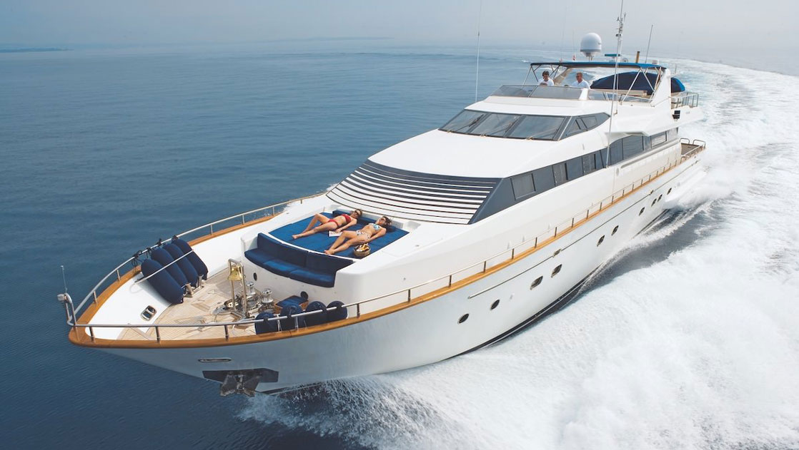 Luxury mega yacht cruises through calm waters at high speed, with 2 women in bikinis laying on blue cushions on the bow.
