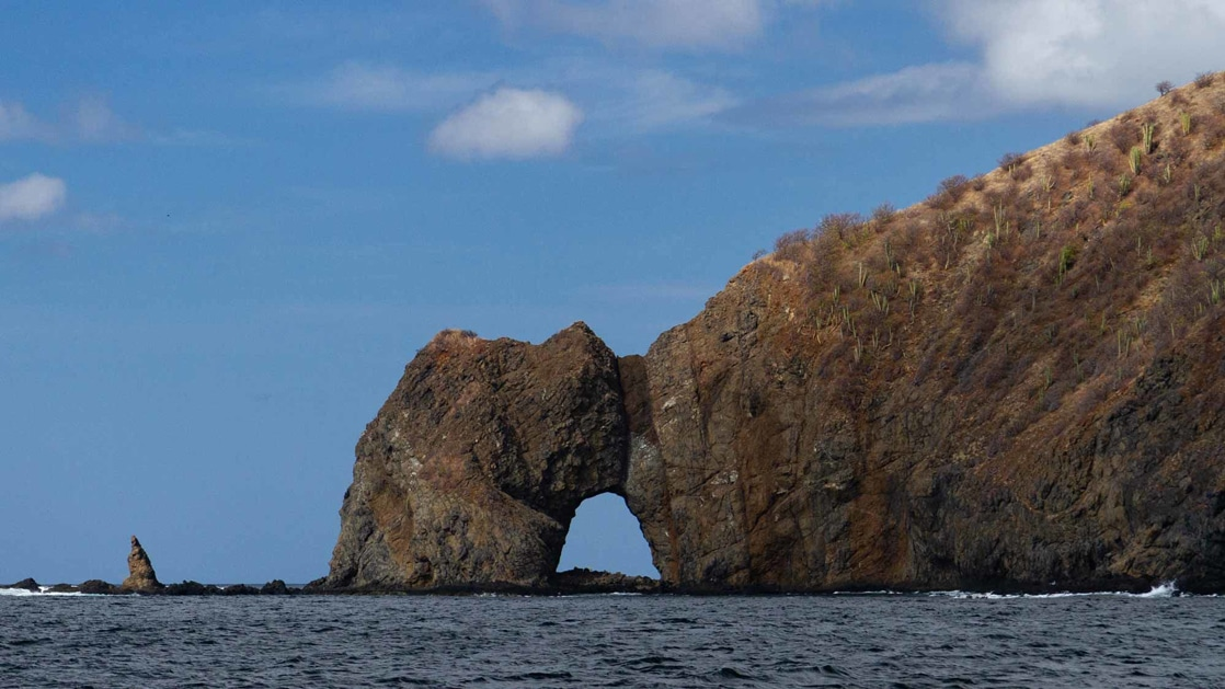 A massive brown rocky arch extends from the dark blue ocean and into bright blue the sky around the Bat Islands of Costa Rica.