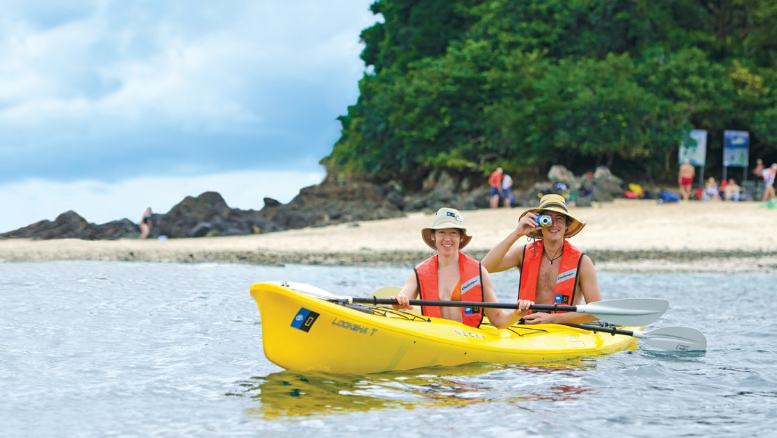 Two male travelers wear orange life jackets and tan wide brimmed hats paddle a yellow double kayak off the coast of Costa Rica.