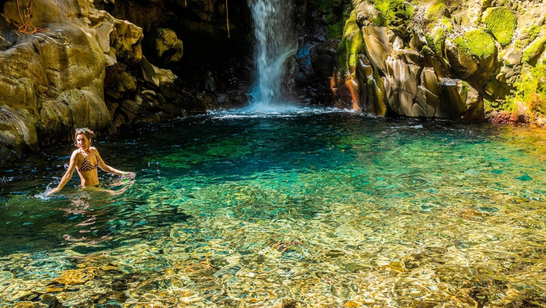 A girl in a bikini wades into a clear turquoise pool beneath a small waterfall inside forest of a Costa Rican jungle.