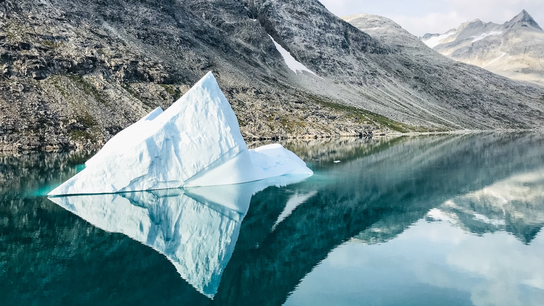Tiny iceberg floats in glassy reflective waters of a fjord with rocky gray peaks beside, seen on the Wild Greenland Escape voyage.
