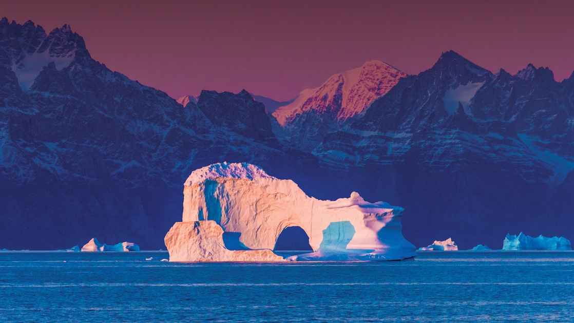 Large white iceberg with an arch in its center sits in purple light at dusk during the Wild Greenland Escape small ship voyage.