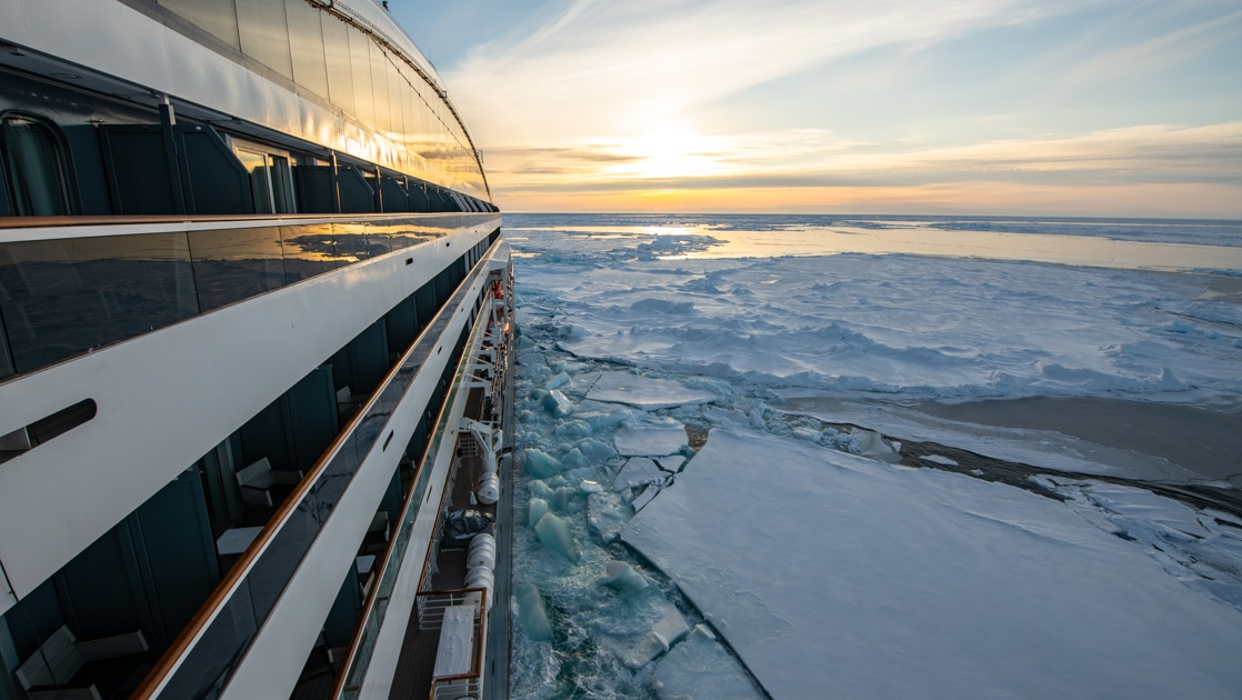 View of side of a small, modern expedition ship as it cruises through ice at sunset on the Commandant Charcot North Pole Expedition.