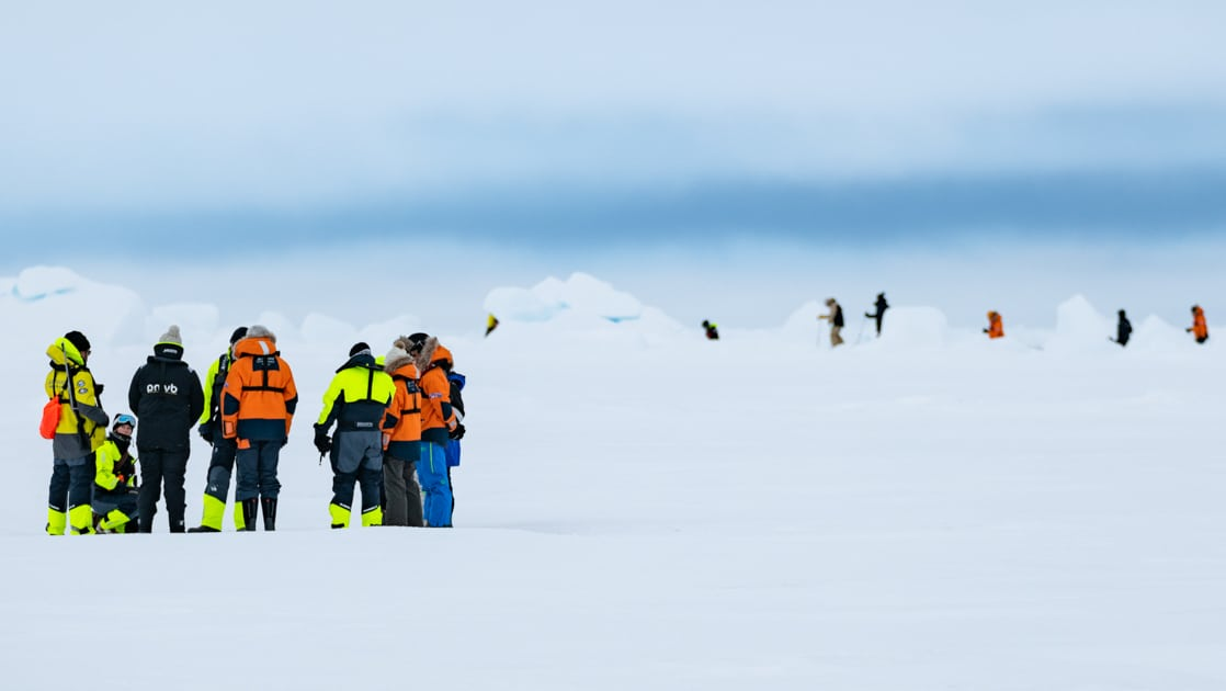 Group of polar travelers in bright jackets stand atop ice & snow during the Le Commandant Charcot North Pole Expedition.