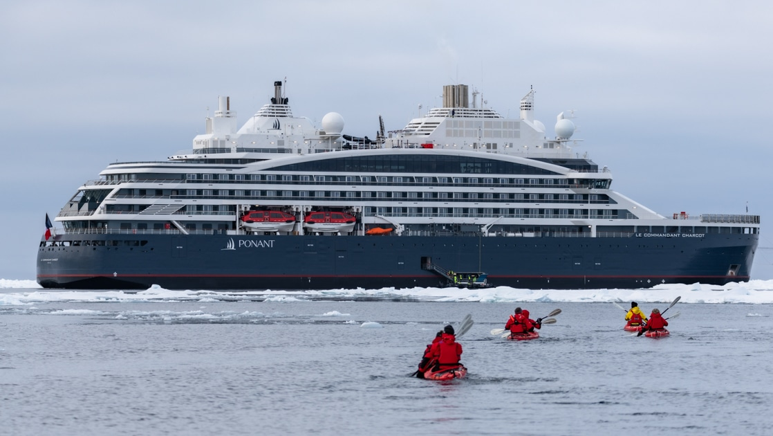 Dark blue & white expedition ship sits beside ice as travelers in red jackets & kayaks paddle beside on a luxury North Pole voyage.