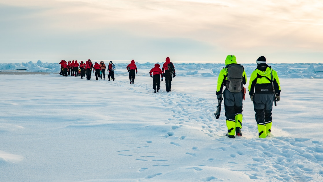 Polar travelers in red jackets walk in a group with 2 guides in neon jackets following behind, on a cloudy day at the North Pole.