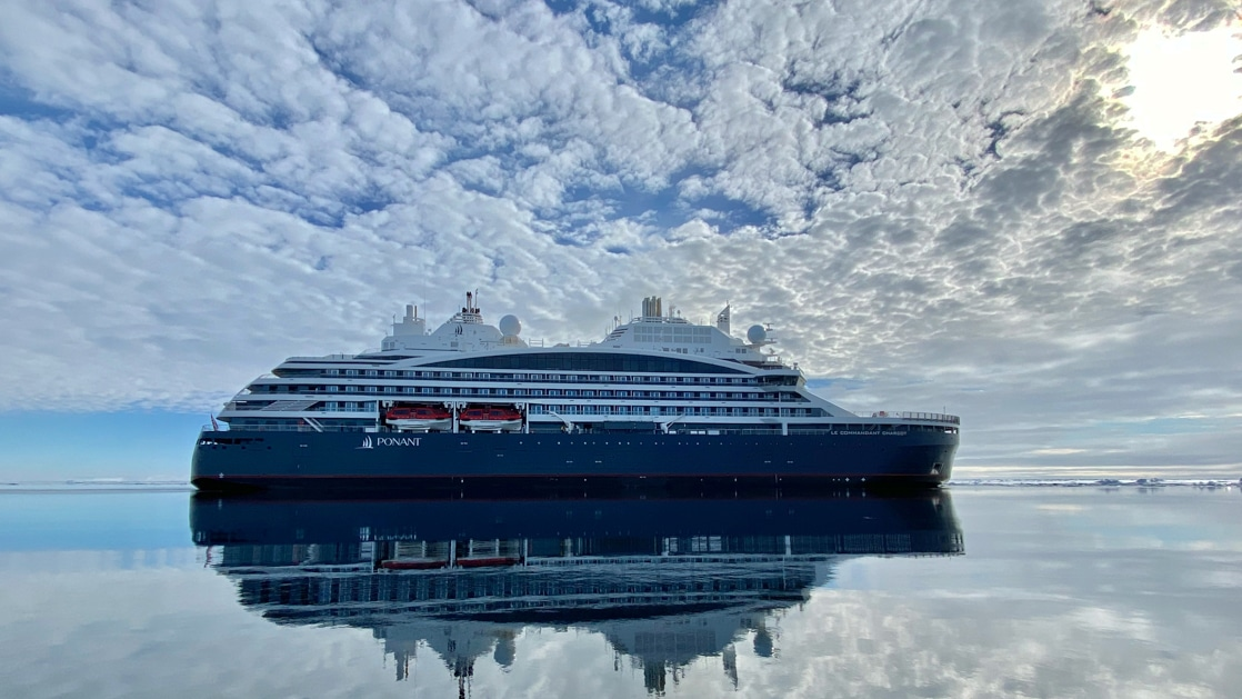 Arctic expedition ship with dark blue hull & white upper decks sits in glassy water under a partly cloudy sky.