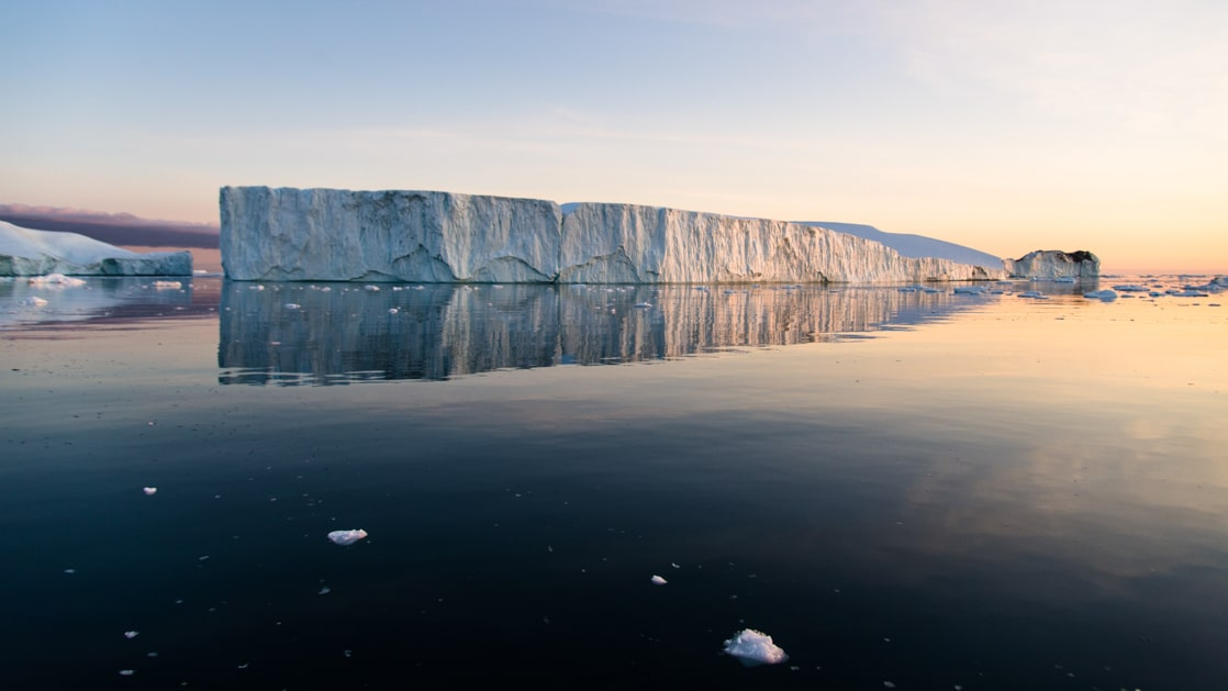 Large iceberg floats in glassy water at dusk, seen on Le Commandant Charcot Svalbard Voyages.