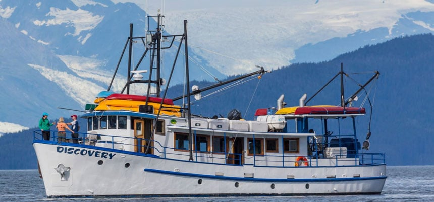 Small ship to Alaska Discovery with 2 passenger decks in white with blue trim sits in calm water beside green mountains in Alaska.