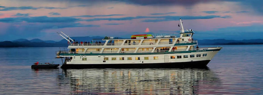 3-passenger-deck small ship to Alaska in white & turquoise with a black hull, cruising in calm water at sunset.