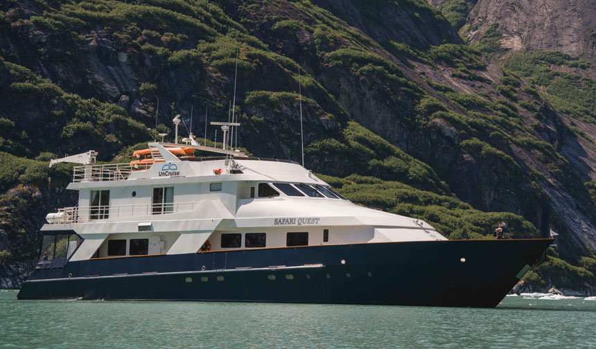 Safari Quest Alaska motor yacht with 3 passenger decks in white & dark blue sits beside green mountains in calm milky waters.